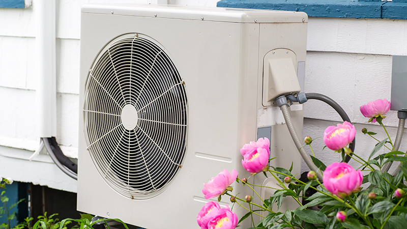 Air conditioning/ heat pump unit on the side of a home among the flowers
