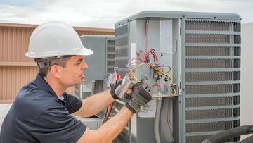 HVAC technician working on a capacitor part for condensing unit